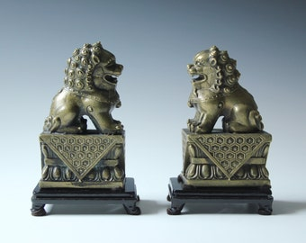 Pair of brass foo dogs lion figures with wood stand