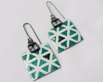 Enameled earrings in turquoise and white with pattern of triangles. Made of sterling silver and copper