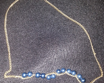 Gold chain with pearlescent blue beads