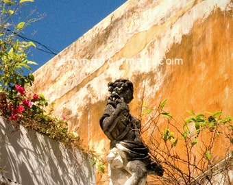 Photography: statue on old rustic building rooftop garden, textured wall, warm colours golden yellow, intense blue. Shabby chic, zen art.