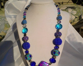 Statement necklace in various shades of blue and purple with glass and metal accent beads