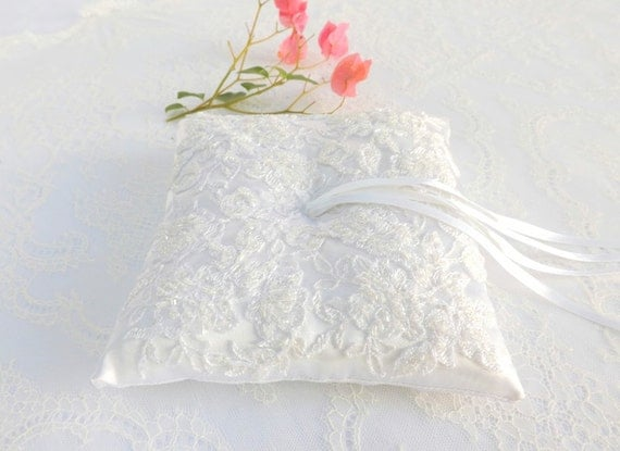 White wedding ring pillow. White satin ring bearer decorated with embroidered lace flowers.
