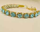 Handmade leather wrapped crystal bracelet. Aqua crystals on raw brass, light chartreuse green leather. One size, adjustable