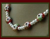 Christmas necklace of white pearls and red puffed disks embellished with white poinsettias and trimmed with black, white and green accents