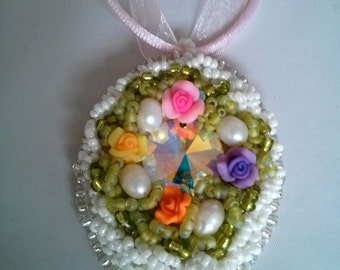 pretty beaded floral pendant on a pink ribbon