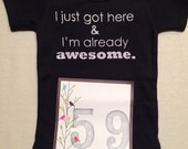 DISCOUNTED -- Nearly Perfect -- #59b, see photos -- I just got here & I'm already awesome.  -- black snapsuit, size 0-3 months