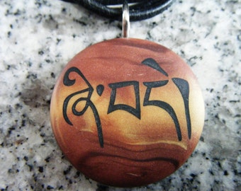 Tibetan-Peace Pendant hand carved on a polymer clay bronze/light gold color background.  Comes with a FREE necklace