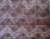 Large sheet brown tissue paper, handprinted in white zigzag linoprint.