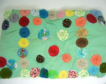 46 vintage yoyo quilt pieces on green and cream cotton pillowcase, handmade supply to upcycle fabric, mixed media art or restuff pillow.