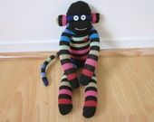 Dark rainbow sock monkey doll with muted neon stripes and black background