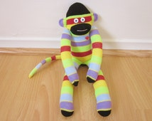 80s striped sock monkey plush doll with neon green, red, blue, purple, and yellow stripes and black accents