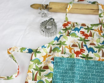 Dinosaurs and Volcanos Child Apron with teal dinosaur words pocket
