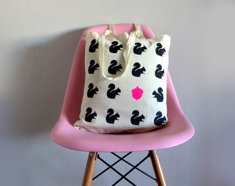 Woodland tote bag with black squirrels and neon pink acorn. Natural cotton.