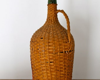 Vintage portuguese green glass wine bottle encased in a straw basketry