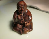 netsuke hand carved PIPE SMOKING GENTLEMAN heavy detailed carving cherry stain on birch wood 2 inches very collectible