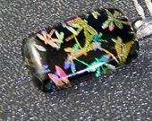3D Dichroic Dragonfly pendant, gold, pink, blue, green on black background
