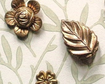 Botanical buttons, vintage, 3 different - l diminutive & 2 small, pressed metal, 2 flowers and one leaf.  c early 20th. cent. to 1930's.