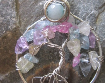 Spring tree of life in silver coloured metal with cracked quartz in pinks, yellows and blues