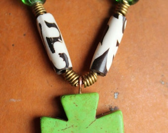 Cross pendant with turqoise heart bead and black and white bone beads and green glass beads