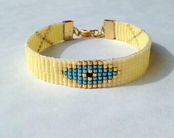 Evil eye woven beaded pastel yellow friendship bracelet.