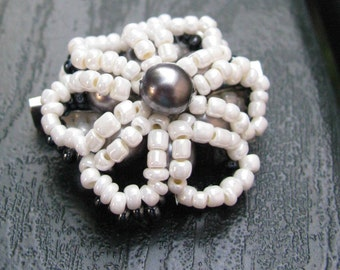 Daisy-shaped brooch of rocailles pearls and beads