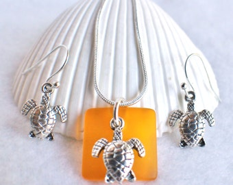 Sea glass necklace in orange with tibetan silver sea turtle charm on chain with matching earrings.