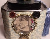 Altered art tea tin with antique graphic and buttons.