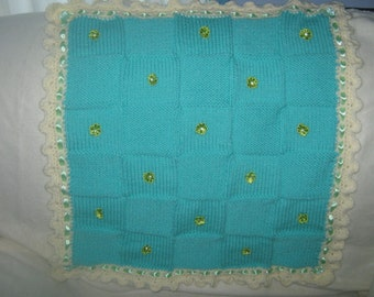 a chunky knit green and white baby,s blanket