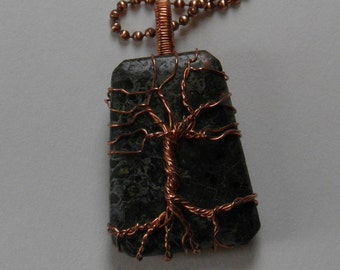 Copper tree of life necklace over a Kambaba Jasper stone.