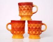 Three Orange FireKing Coffee Cups in the Diamond Kimberly Pattern