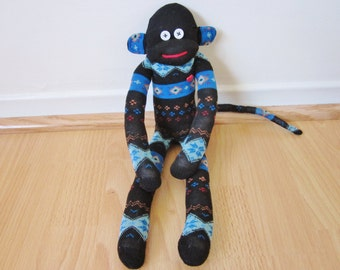 Black, electric blue, red, and orange sock monkey plush with red heart