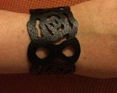 Black faux leather flower cut out bracelet