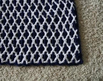 Navy blue and white interlocking crochet afghan