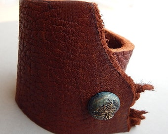 Soft leather cuff with hand carved cast landscape snap.
