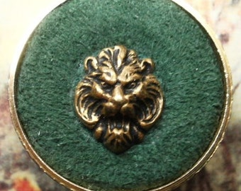 """Textile button, vintage, a """"drum"""" with a green suede background & a lions head escutcheon in the centre. c1950's to 70's."""