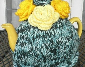 Hand knitted 'Taste of Summer' tea cosy in shades of green with vibrant yellow roses for House Tyrell fans