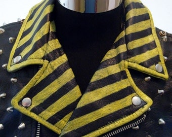 Studded black leather vest with hazard stripes.