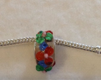 A Green and Red Flower Charm.