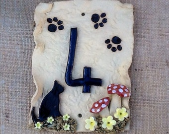 House number plaque, ceramic door numbers, cat and paw prints.