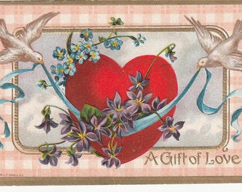1910 A Gift Of Love Red Heart Doves Pulling Ribbon With Blue&Purple Flowers Postcard