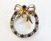 Vintage rhinestone Christmas wreath brooch pin with bow green clear red stones gold tone metal