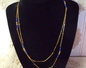 Vintage long gold chain with royal blue and gold bead accents.