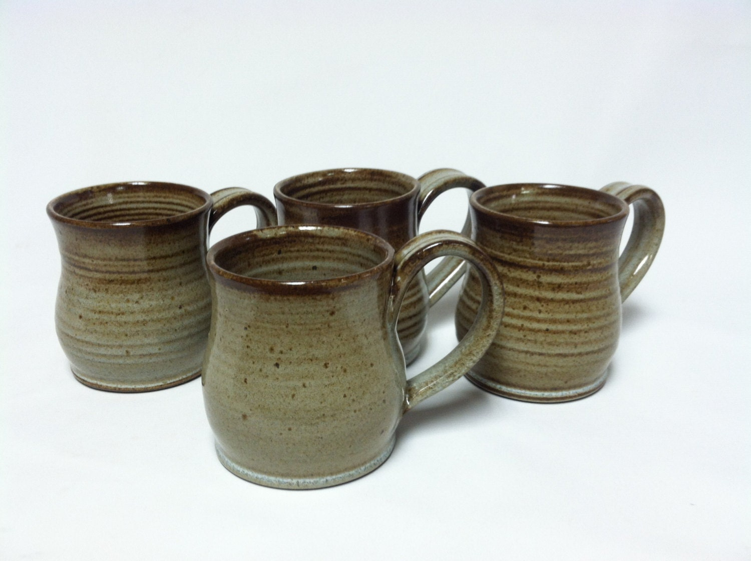Beautiful Le Creuset stoneware coffee mug with a pearlescent dark green finish on the outside and solid light beige interior. Excellent condition with no chips, cracks, or scratches!