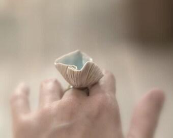 Porcelain mushroom ring with aqua glaze and adjustable band.