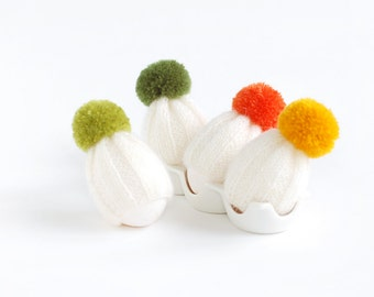 Egg warmers in white with colorful poms. Set of 4.