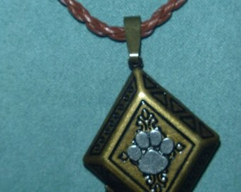 Diamond shaped embossed with dark lines locket with lead free pewter paw brown cord
