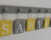 Nursery Name Sign, Baby Name Plaque, Personalized Nursery Baby Name with Grey Peg Board | Yellow & Gray Hanging Wooden Wall Art Above A Crib