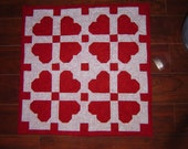 Quilted hearts on a beautiful table mat or wall hanging. approx 33 inches square.