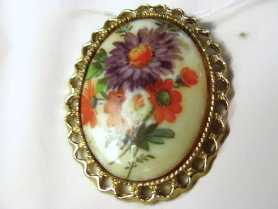 1960s oval goldtone plaque two inch resin brooch with decopauged flowers in purple and orange