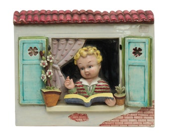 Vintage porcelain tile of a child reading near a window